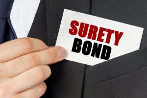 Business concept. Businessman holds a card with the text - SURETY BOND